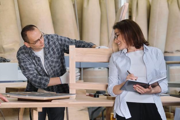 Trabalhando marceneiro masculino e proprietário da empresa feminina com notebook na oficina de madeira