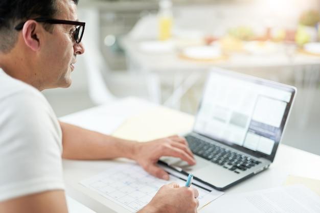 Trabalhando mesmo de longe. perto do homem latino focado, usando seu laptop e marcando os dias no calendário enquanto trabalhava na área de trabalho. trabalhe online.