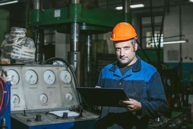 Trabalhando na fábrica com o tablet em mãos no fundo do equipamento