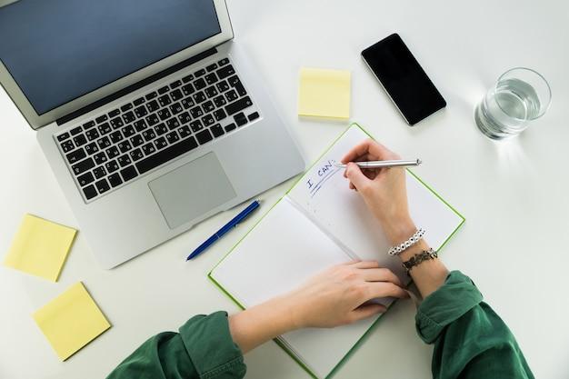 Trabalhando na mesa com o bloco de notas e o computador portátil