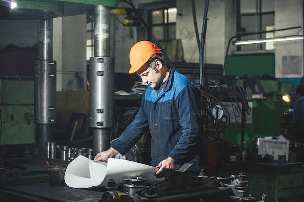 Trabalhando na produção em um pano de fundo de máquinas dos desenhos de engenharia