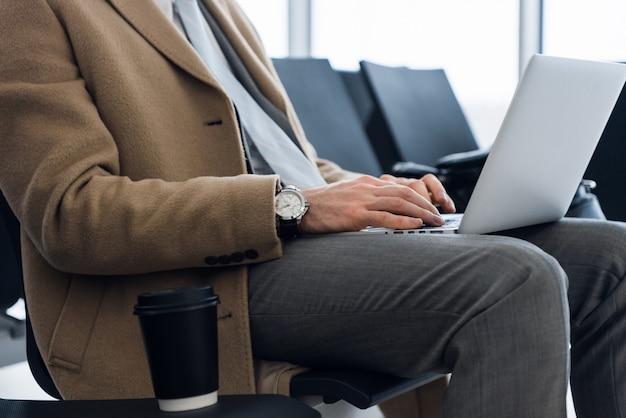 Trabalhando no laptop, close-up das mãos do homem de negócios