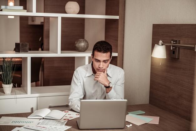 Trabalhando no laptop. homem de negócios inteligente e habilidoso de cabelos escuros trabalhando em um laptop sentado em um quarto de hotel