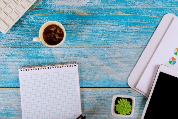 Trabalhando no teclado do computador em uma xícara de café expresso com notebook em branco