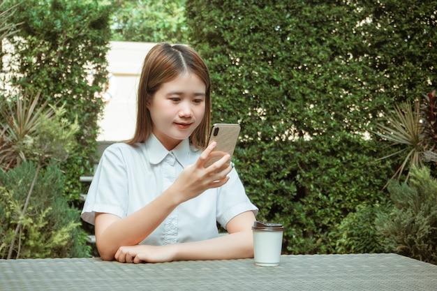Trabalhando o conceito ao ar livre, uma adolescente sentada pacificamente em um jardim