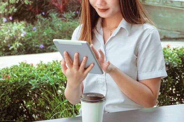 Trabalhando o conceito ao ar livre, uma aluna adolescente usando seu tablet, participando de aulas online no jardim de sua casa.