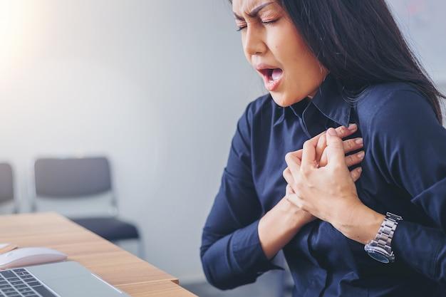 Trabalhando o rosto de mulher, sofrendo e segurando o peito por causa do infarto do coração no escritório