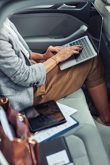Trabalhando online em táxi, tiro vertical de mulher de negócios usando laptop enquanto está sentado no banco de trás do