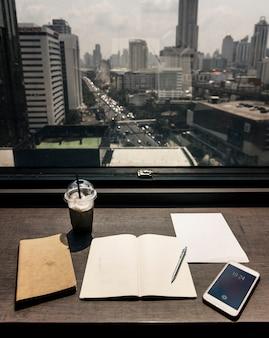 Trabalhando pela janela em uma mesa de madeira