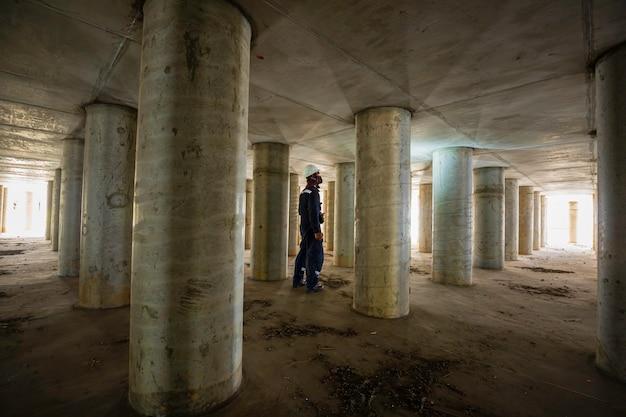 Trabalhando pólo de inspeção masculino subterrâneo do túnel de equipamento do tanque usando a lanterna dentro do tanque.