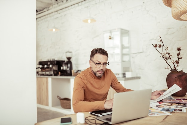 Trabalhando remotamente. designer de moda focado olhando para seu laptop na mesa em casa.