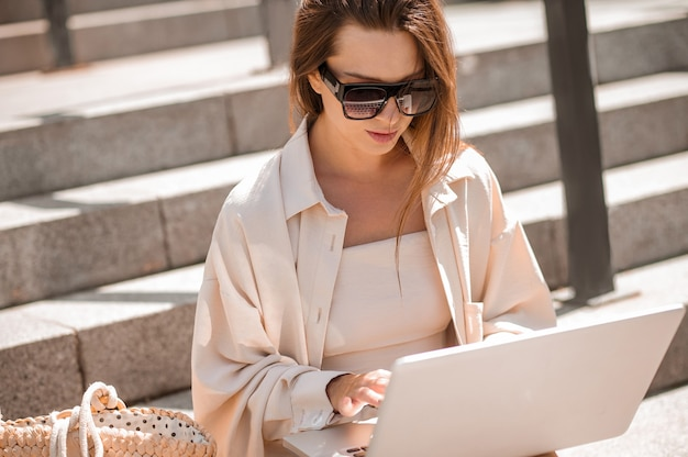 Trabalhando remotamente. uma mulher de óculos escuros sentada nos degraus e trabalhando em um laptop