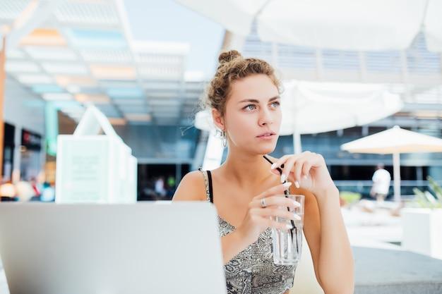 Trabalhar ao ar livre. linda mulher com um chapéu descolado trabalhando em um laptop e sorrindo enquanto está sentado ao ar livre