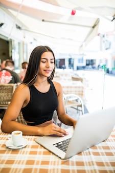 Trabalhar ao ar livre. mulher jovem e bonita com chapéu descolado, trabalhando em um laptop e sorrindo enquanto está sentado ao ar livre