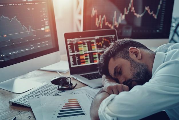 Trabalhar até tarde. jovem empresário exausto em trajes formais dormindo sentado no escritório
