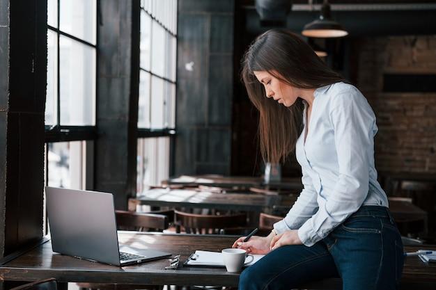 Trabalhar com documentos. mulher de negócios com roupas oficiais está dentro de casa no café durante o dia.