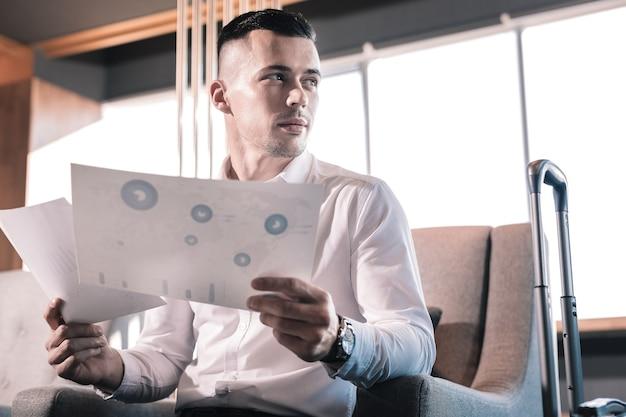 Trabalhar com documentos. perto de um homem próspero bonito usando um relógio de mão e trabalhando com documentos
