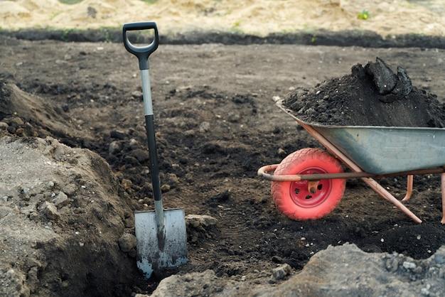 Trabalhar com ferramentas de jardim, pá e carrinho de mão no local de uma preparação de casa de campo para