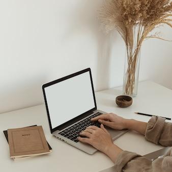 Trabalhar em casa conceito. garota trabalhando no laptop. plano de fundo estético do espaço de trabalho minimalista.