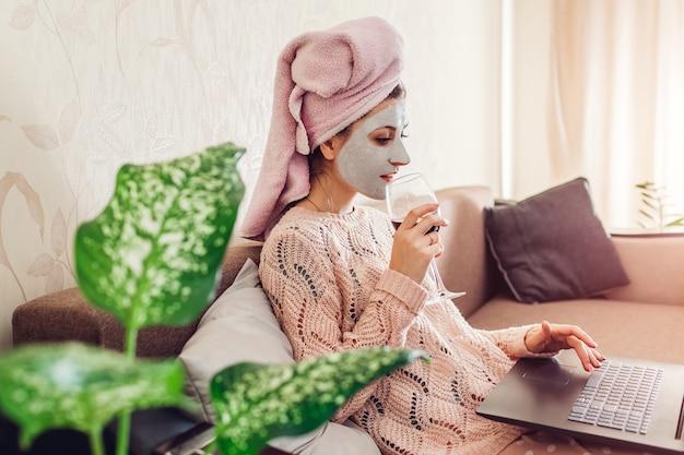 Trabalhar em casa durante a quarentena de coronavírus. mulher com máscara facial aplicada bebendo vinho usando laptop no bloqueio