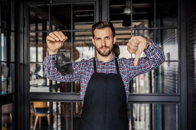 Trabalhar em um restaurante durante a pandemia do coronavírus. garçonete segurando a máscara e mostrando o polegar para baixo.