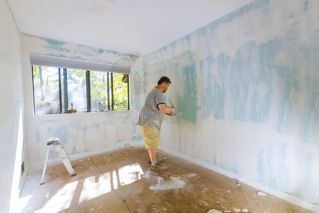 Trabalhar parede com ferramenta manual usando ferramenta de gesso para acabamento de parede