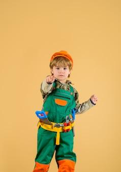 Trabalhe com conserto de ferramentas garotinho com uniforme de construtor com cinto de ferramentas garotinho reparador apontando