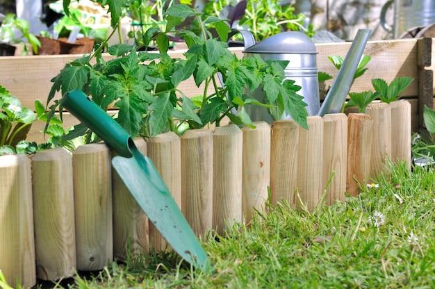 Trabalhe com pá contra uma borda de madeira em um jardim