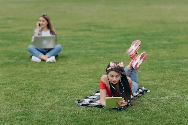 Trabalhe como freelancer. relaxe e seja feliz. aprendizagem do aluno. dois amigos de meninas bonitas sentado na grama verde.