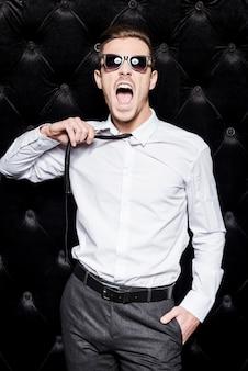 Trabalhe duro jogue duro! jovem bonito usando óculos escuros tirando a gravata e gritando em pé contra um fundo preto