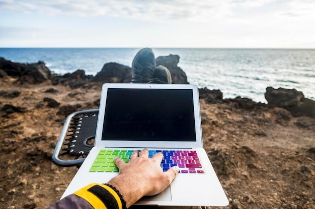 Trabalhe e fique conectado com a internet e o conceito de laptop mão no teclado relaxando e trabalhando em frente à natureza do oceano escritório alternativo ao ar livre para o viajante desfrutando de um estilo de vida livre