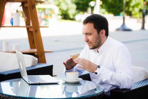 Trabalhe e relaxe. conferência online. empresário, vestido de camisa, trabalhando com o laptop, falando pelo skype no café do parque ao ar livre