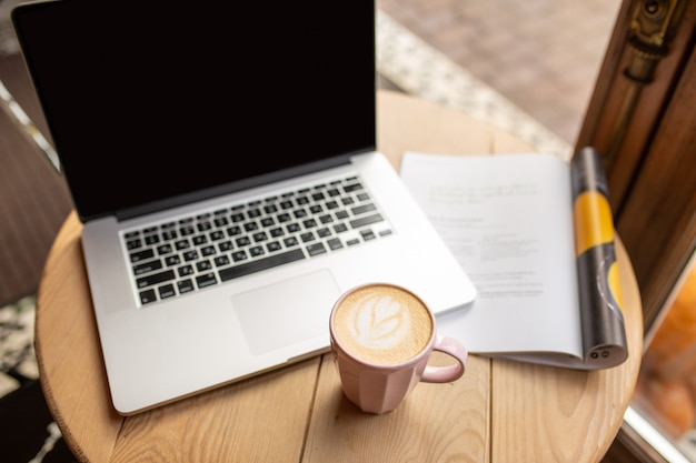 Trabalhe em casa com uma xícara de café. ambiente doméstico com um processo de trabalho. hora para você. hora de tomar café. café com leite com um laptop. café da manhã com trabalho. leia as notícias durante o coronavírus