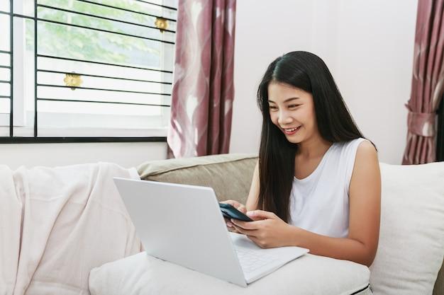 Trabalhe em casa e o conceito de compras online. mulher asiática de negócios feliz usando telefone celular e laptop com notebook no sofá na sala de estar em casa