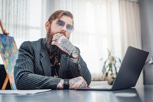 Trabalhe em casa. homem vestido com um terno elegante com óculos de sol se senta à mesa com um laptop. cara brutal e seu trabalho remoto.