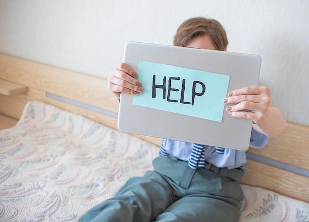 Trabalhe em casa. menina cansada segurando um laptop e uma placa com o texto ajuda
