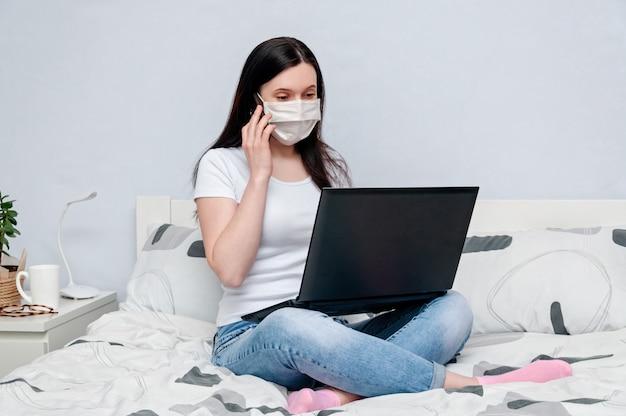 Trabalhe em casa ou a distância, em quarentena. mulher em máscara protetora trabalhando remotamente na cama usando o laptop e falando no telefone.