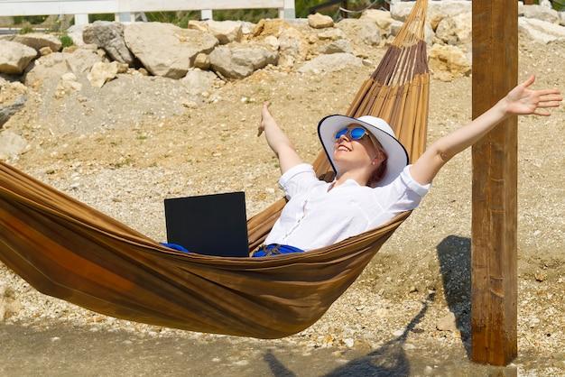 Trabalhe em qualquer lugar. jovem sorridente, mulher, freelancer, mulher, chapéu de palha, trabalhando em um laptop na praia