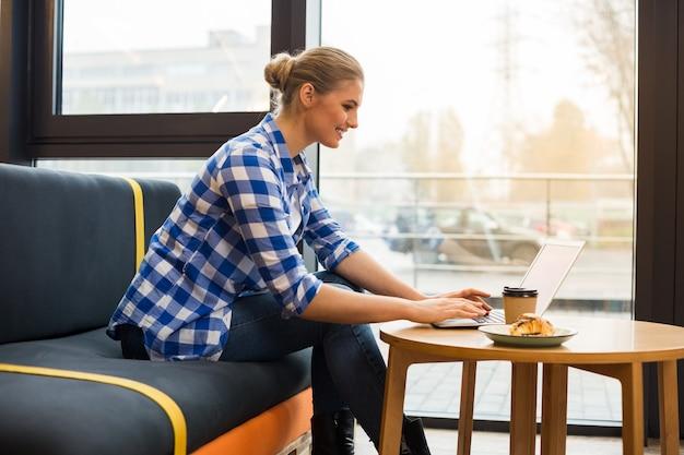 Trabalho à distância. mulher autônoma positiva e simpática, sentada à mesa e usando o laptop enquanto trabalha no café