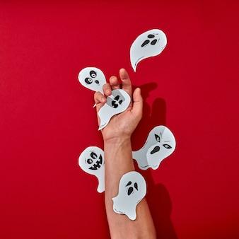 Trabalho artesanal de papel vários fantasmas decoram a mão de um homem sobre um fundo vermelho com espaço para texto. composição criativa de halloween. postura plana