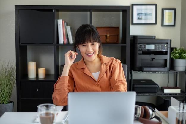 Trabalho asiático da mulher no escritório do portátil do computador em casa. videochamada, estudando, aprendendo e trabalhando on-line.