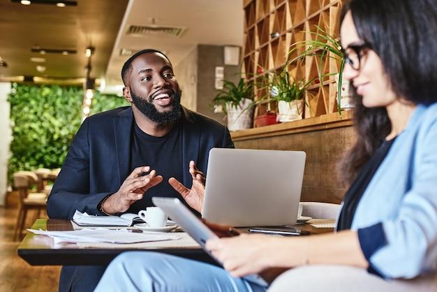 Trabalho com alegria e paz mulher séria ouvindo seu colega durante o almoço no café