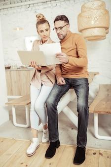 Trabalho comparativo. designer de moda concentrado comparando seus esboços a fotos em um laptop nas mãos de sua assistente.