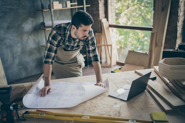 Trabalho concentrado de trabalhador perto da mesa com plano de construção branco olhar na oficina de construção de relógio de computador na garagem de casa