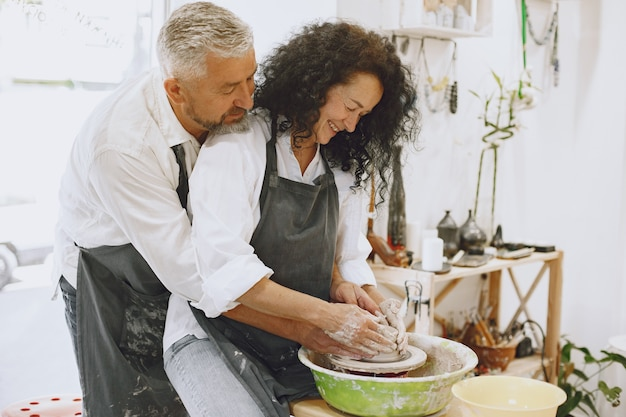 Trabalho criativo mútuo. casal adulto elegante com roupas casuais e aventais. pessoas criando uma tigela em uma roda de oleiro em um estúdio de argila.