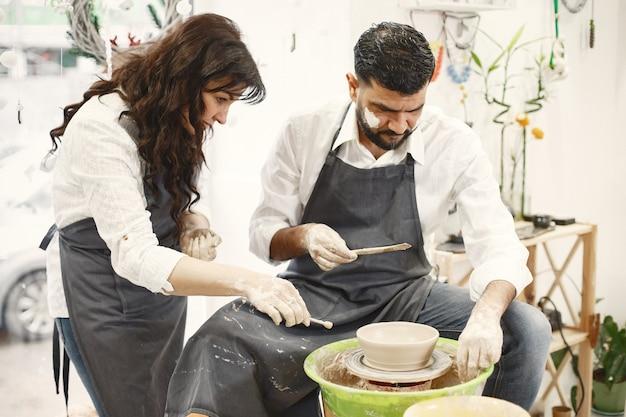 Trabalho criativo mútuo. casal elegante com roupas casuais e aventais. pessoas criando uma tigela em uma roda de oleiro em um estúdio de argila.