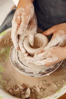 Trabalho criativo mútuo. jovem casal lindo em roupas casuais e aventais. pessoas criando uma tigela em uma roda de oleiro em um estúdio de argila.