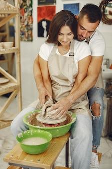 Trabalho criativo mútuo. jovem casal lindo em roupas casuais e aventais. pessoas criando uma tigela em uma roda de oleiro