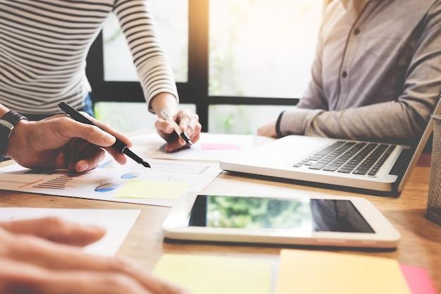 Trabalho da equipe criativa. o jovem homem de negócios que trabalha com o projeto de inicialização analisa os planos do gráfico e discute no escritório do espaço de trabalho, o conceito de reunião do brainstorm.