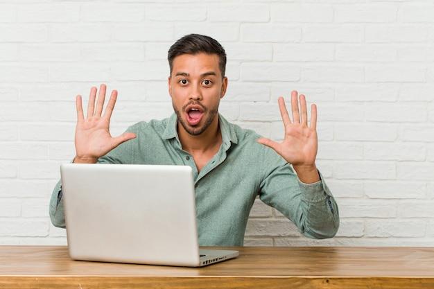 Trabalho de assento do homem filipino novo com seu portátil que mostra o número dez com mãos.